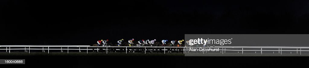 Runners make their way down the back straight in The BetVictor 'Jumpers' Bumper' National Hunt Flat Race lit by floodlights at Kempton racecourse on January 25, 2013 in Sunbury, England.