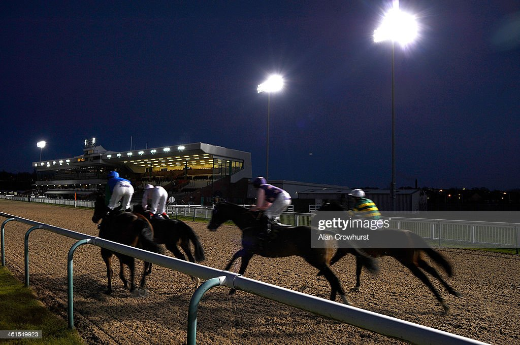 Runners make their way past the grandstands in The Ladbrokes Handicap Stakes at Wolverhampton racecourse on January 09 2014 in Wolverhampton England