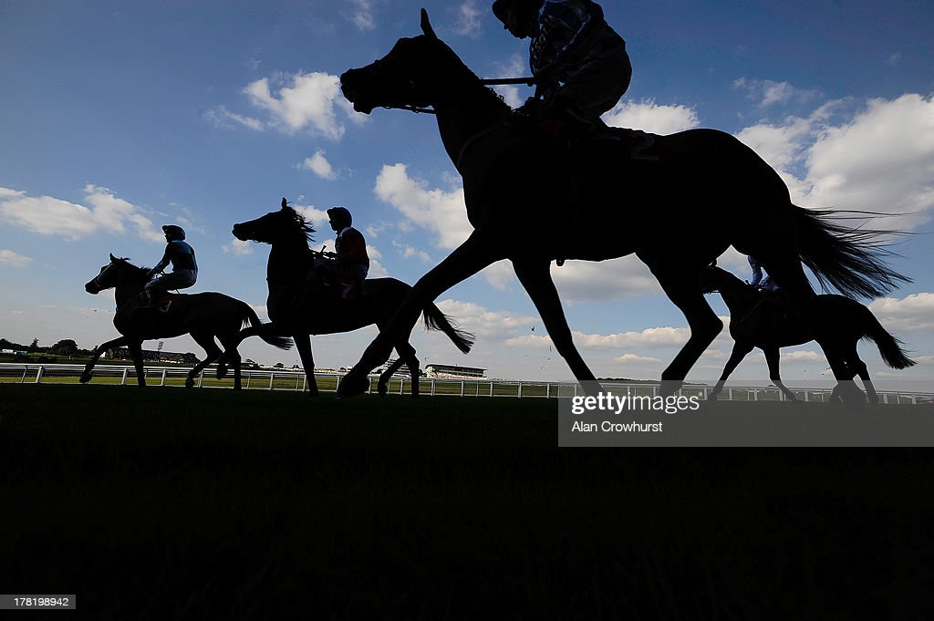 Runners make their way to the start for The Chantilly Handicap Stakes at Epsom racecourse on August 27, 2013 in Epsom, England.
