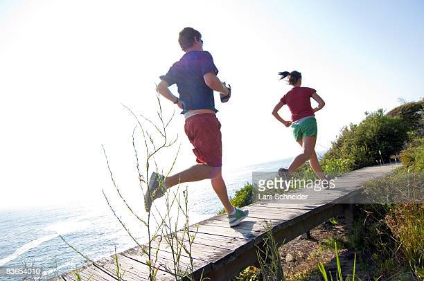 Runners on bridge along ocean trail.