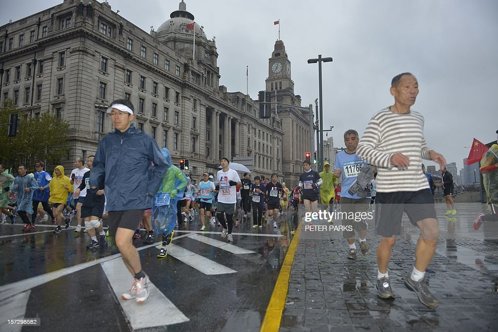 Runners participate in the Shanghai International Marathon on December 2, 2012. Thousands of runners started along Shanghai's famous Bund in the pouring rain for a full, half and fun marathon events. AFP PHOTO/Peter PARKS