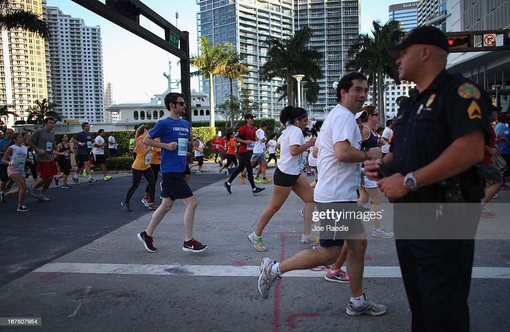 Runners participating in the Mercedes-Benz Corporate Run pass a City of Miami policer officer as security is stepped up after the bombing at the Boston Marathon on April 25, 2013 in Miami, Florida. More than 20,000 people participated in the run.