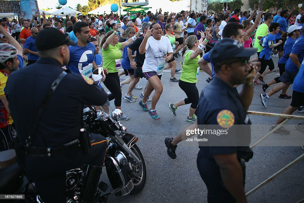 Runners participating in the Mercedes-Benz Corporate Run past City of Miami policer officers as security is stepped up after the bombing at the Boston Marathon on April 25, 2013 in Miami, Florida. More than 20,000 people participated in the run.