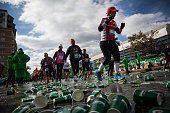 Runners participating in the TCS New York City Marathon pass by a water station on November 2 2014 in the Park Slope neighborhood of the Brooklyn...
