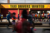 Runners participating in the TCS New York City Marathon pass by taxi depot on November 2 2014 in the Park Slope neighborhood of the Brooklyn Borough...
