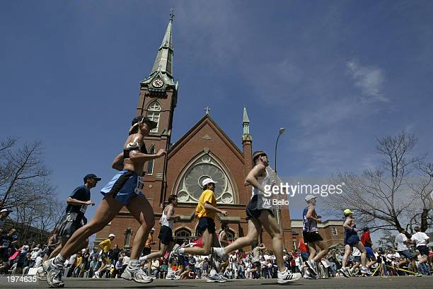 Runners pass a church in the town of Natick during the Boston marathon on April 21 2003 in Natick Massachusetts