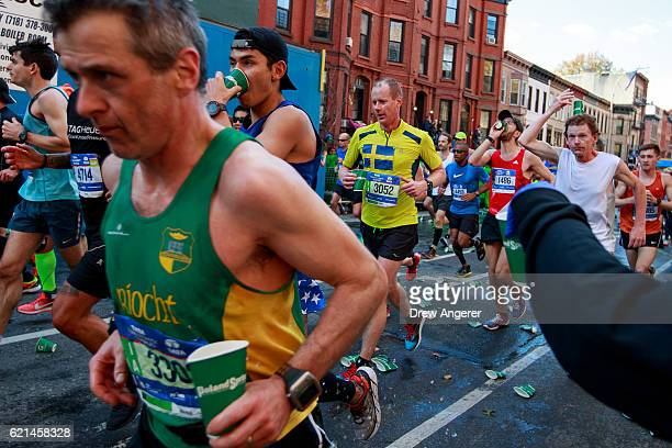 Runners pass a hydration station on Lafayette Avenue during the 2016 TCS New York City Marathon November 6 2016 in the Clinton Hill neighborhood in...