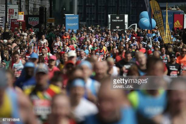 Runners pass Big Ben and the Houses of Parliament during the London Marathon in London on April 23 2017 / AFP PHOTO / Daniel LEALOLIVAS