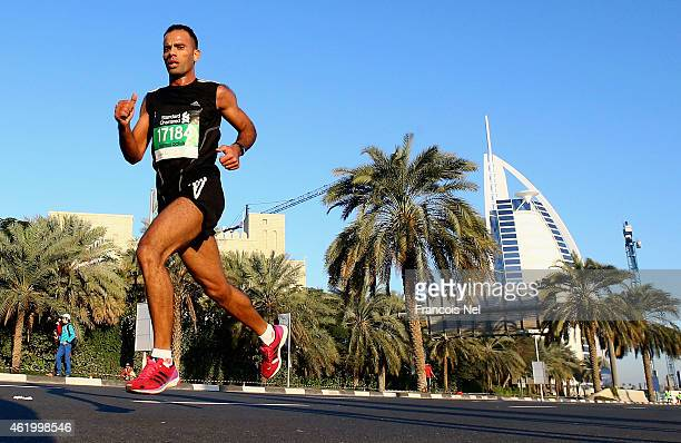 Runners pass Burj Al Arab during the Standard Chartered Dubai Marathon on January 23 2015 in Dubai United Arab Emirates