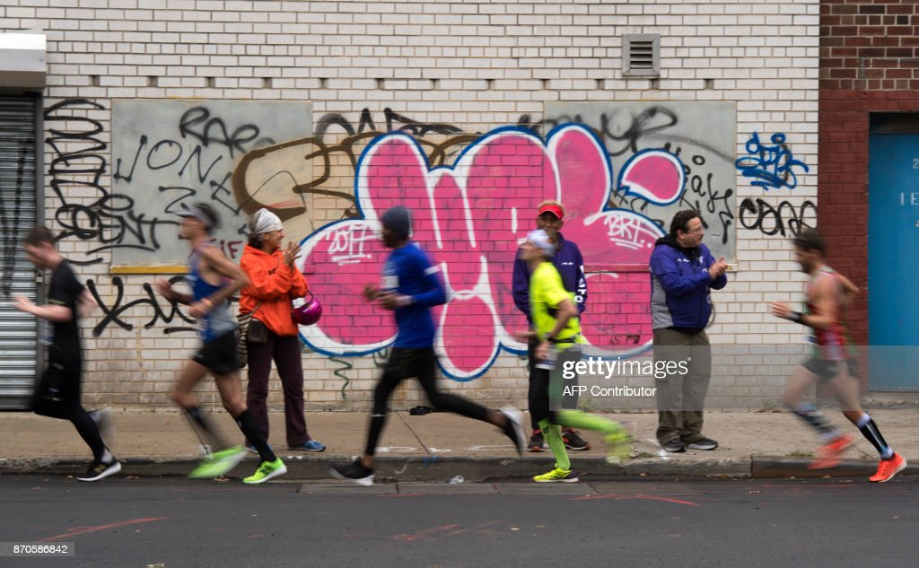 Runners pass graffiti as they make their way through the Bronx as they compete during the 2017 TCS New York City Marathon in New York on November 5, 2017. Five days after the worst attack on New York since September 11, 2001, the city is staging a show of defiance on November 5, as 50,000runners from around the world are set to participate in the New York Marathon, under heavy security. / AFP PHOTO / Don EMMERT
