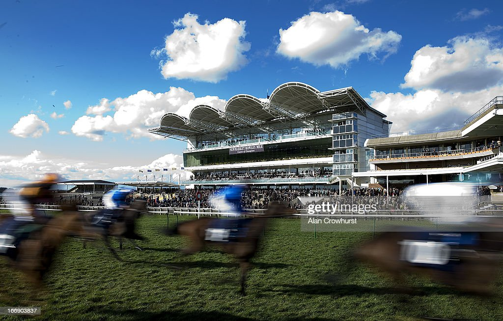 Runners pass the grandstands at Newmarket racecourse on April 18, 2013 in Newmarket, England.