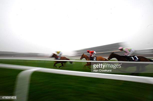 Runners pass the grandstands in The JLT Novices' Steeple Chase on St Patrick's Thursday during the Cheltenham Festival at Cheltenham racecourse on...