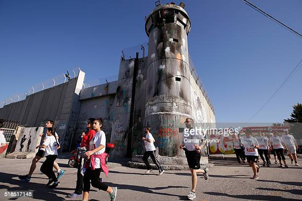 Runners pass the separation wall during the Right to Movement Marathon in the West Bank city of Bethlehem on April 1 2016 in Bethlehem West Bank...