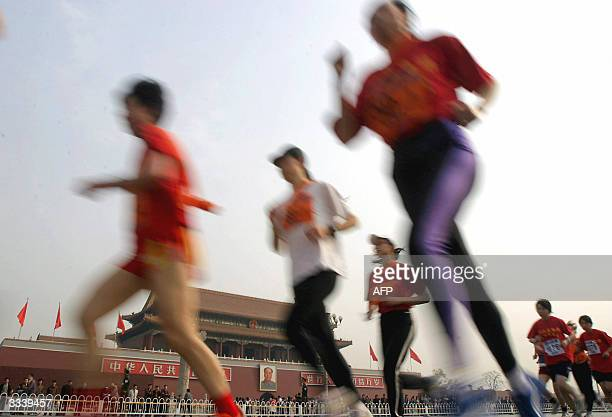 Runners pass the Tiananmen Gate in central Beijing 11 April 2004 at the start of the annual Beijing International Marathon relay race Chinese women...