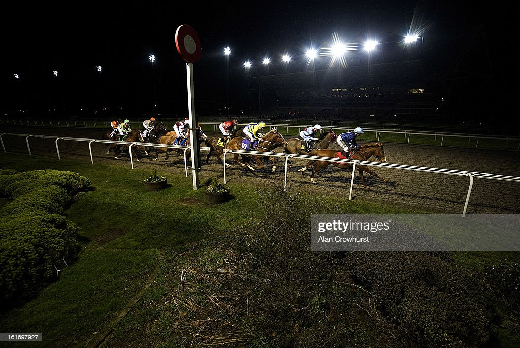 Runners pass the winning post with a circuit to go in The BetVictor Exclusive Non Runner Free Bet Handicap Stakes at Kempton racecourse on February 14, 2013 in Sunbury, England.