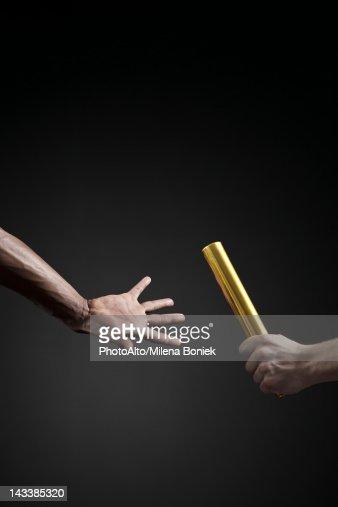 Runners passing baton, cropped
