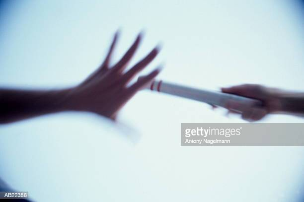 Runner's passing baton, focus on hands (Blurred motion)