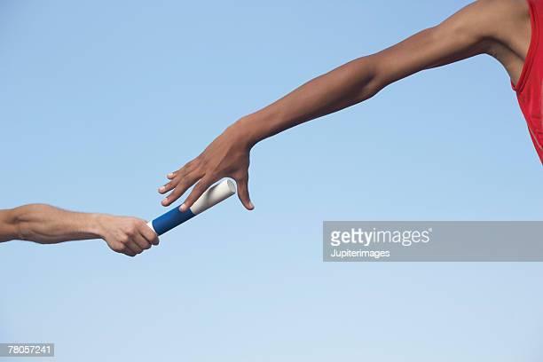 Runners passing baton in relay