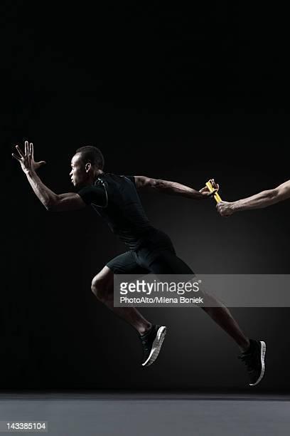 Runners passing baton