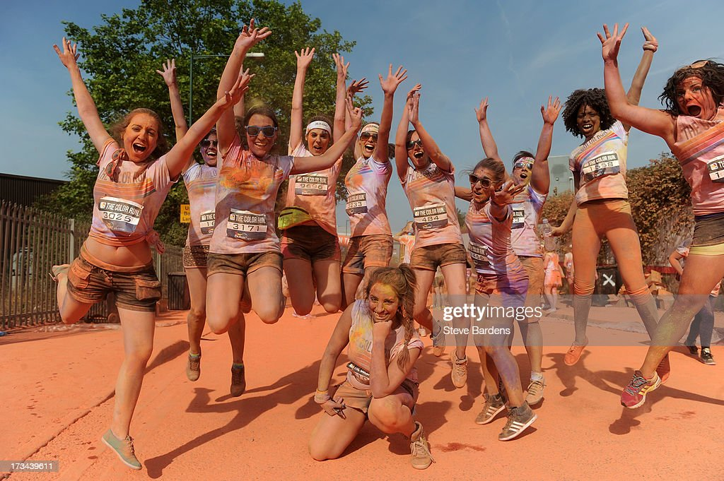 Runners pose for a photograph after going through a Colour Zone at The Color Run presented by Dulux, known as the happiest 5km on the planet, on July 14 in Wembley, England. Runners of all shapes, sizes and speeds start wearing white clothing that is a blank canvas for the kaleidoscope of colours they encounter around The Color Run course. At each kilometre a different colour of powder is thrown in the air with the runners becoming a constantly evolving artwork. At the end of the course runners are greeted by the Colour Festival where the air is filled with music and stunning coloured powder bursts creating a vibrant party atmosphere. www.thecolorrun.co.uk [Media contact: alex.coulson@img.com] on July 14, 2013 in Wembley, England.