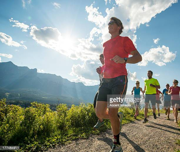 Runners race along path, in mountains