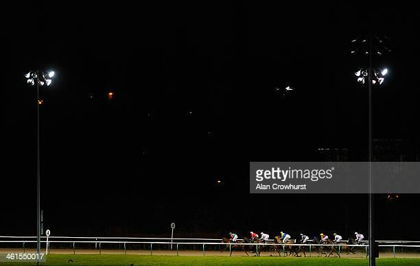 Runners race down the back straight in The Download The Ladbrokes App Handicap Stakes at Wolverhampton racecourse on January 09 2014 in Wolverhampton...