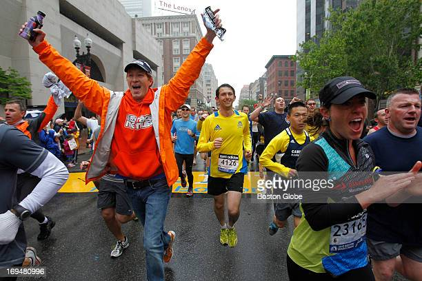 Runners react as they cross the Boston Marathon finish line on Boylston Street during the Boston Strong One Run in Boston on May 25 2013 The event...