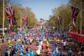 Runners recover after crossing the finish line at the end of the 2014 London Marathon on The Mall in central London on April 13 2014 World...