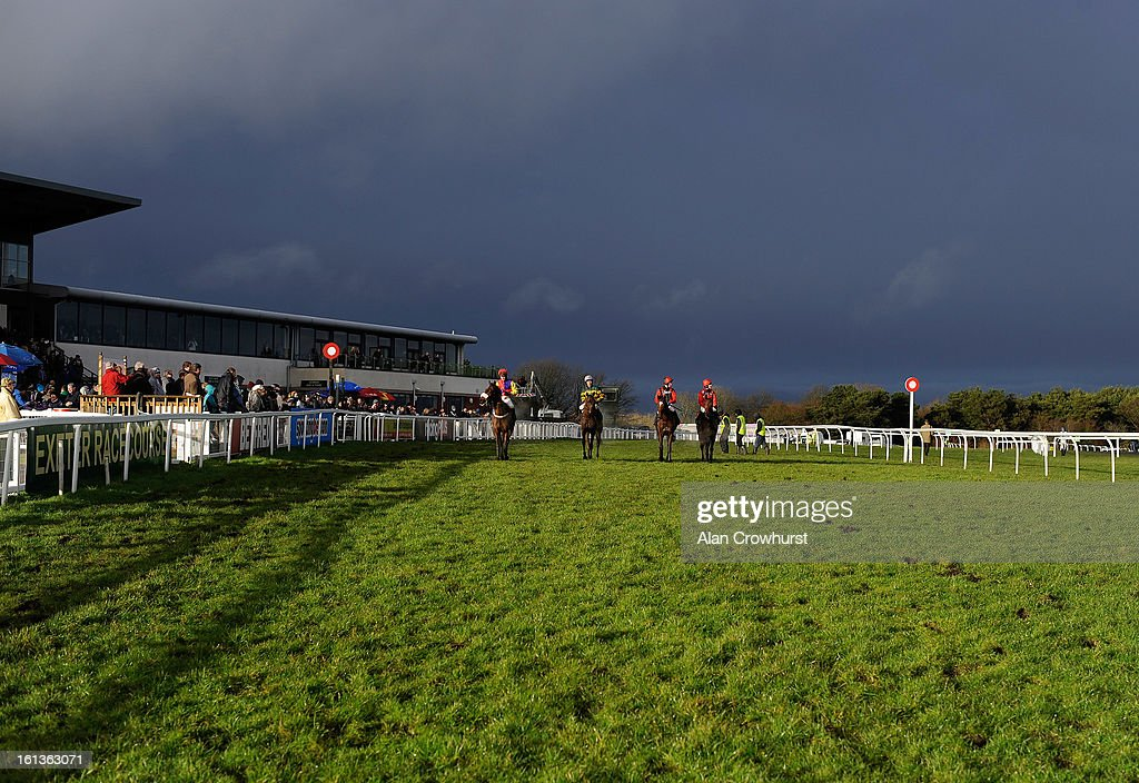 Runners return after finishing as the dark clouds loom at Exeter racecourse on February 10, 2013 in Exeter, England.