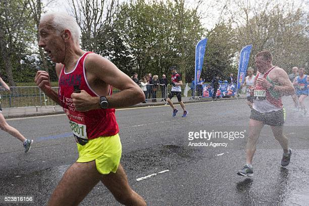 Runners run past rain showers to cool themselves off as they take part in the 2016 London Marathon in London United Kingdom on April 24 2016