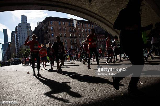 Runners run underneath the 59th Street Bridge during the TCS New York City Marathon on November 2 2014 inof New York City
