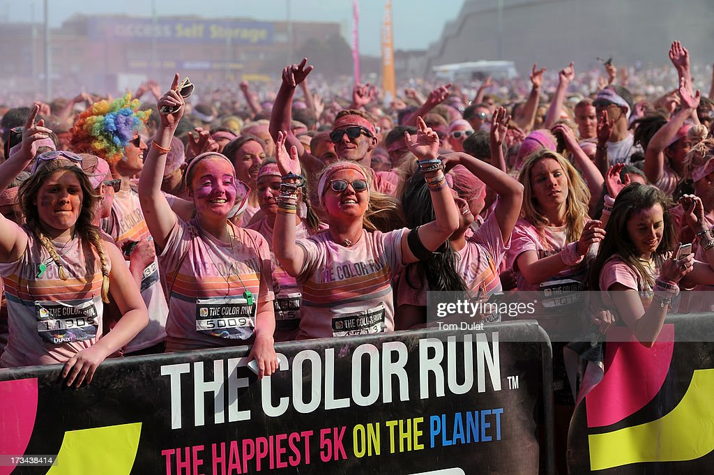 Runners soak up the atmosphere as they dance at The Color Run presented by Dulux, known as the happiest 5km on the planet, on July 14 in Wembley, England. Runners of all shapes, sizes and speeds start wearing white clothing that is a blank canvas for the kaleidoscope of colours they encounter around The Color Run course. At each kilometre a different colour of powder is thrown in the air with the runners becoming a constantly evolving artwork. At the end of the course runners are greeted by the Colour Festival where the air is filled with music and stunning coloured powder bursts creating a vibrant party atmosphere. www.thecolorrun.co.uk [Media contact: alex.coulson@img.com] on July 14, 2013 in Wembley, England.