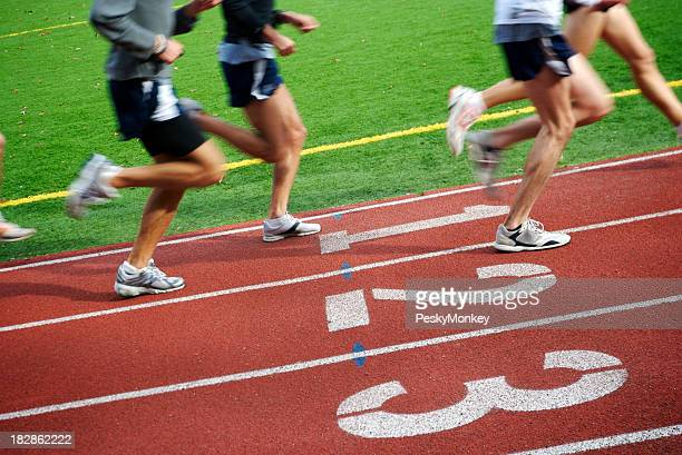 Runners Speed by on Running Track