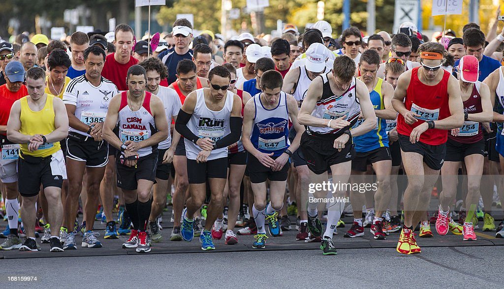 Runners start their timers as they head off from Mel Lastman Square, North York, in the Toronto Marathon.