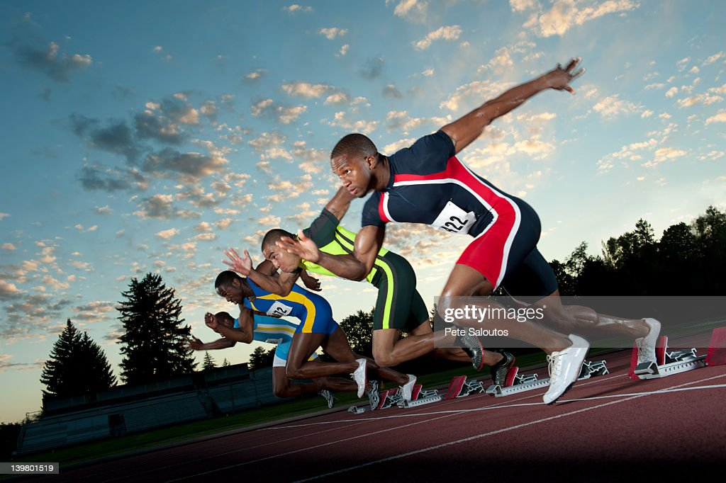 Runners starting on track from starting blocks : Stock Photo