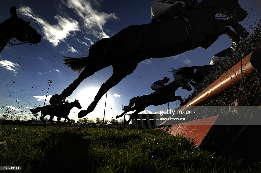 Runners take a fence in The williamhill.com Steeple Chase at Kempton Park racecourse on January 11, 2014 in Sunbury, England.