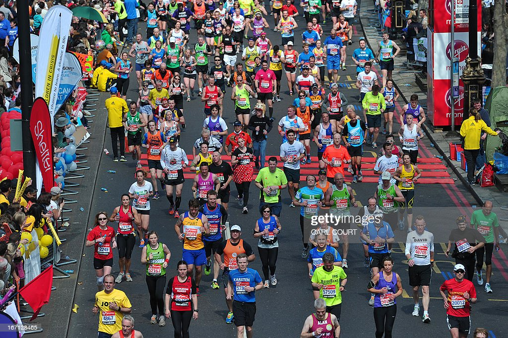 Runners take part in the 2013 London Marathon in London on April 21, 2013. Tens of thousands of runners flowed through the British capital Sunday in the London Marathon, after a solemn 30-second silence at the start for the victims of the bomb attacks at the Boston Marathon barely a week ago. AFP PHOTO / CARL COURT RESTRICTED TO EDITORIAL USE / NO COMMERCIAL USE