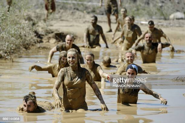 Runners take part in the Mud Day a 13km race with obstacles on April 8 at the Lac de Peyrolles near Aix en Provence southern France / AFP PHOTO /...