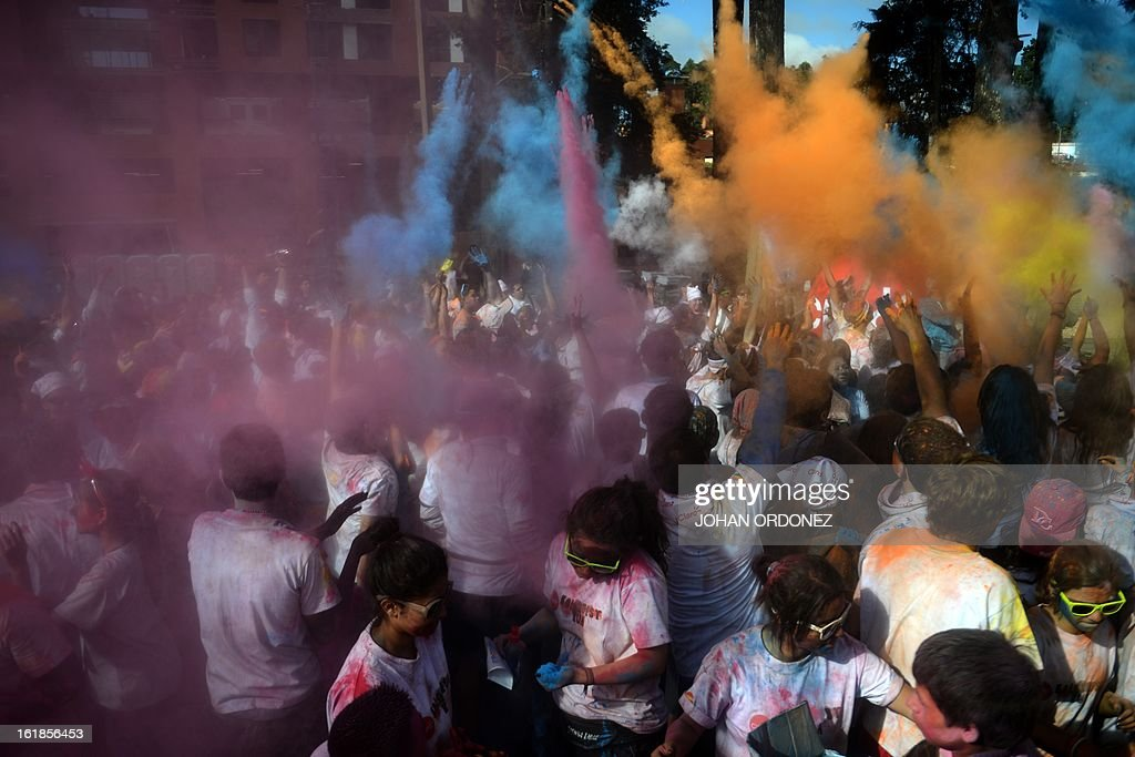Runners throw paint powder at the finish line of the Kolorfest race in Guatemala City on February 17, 2013. About 1500 people participated in the event to raise money for charities. AFP PHOTO/Johan ORDONEZ