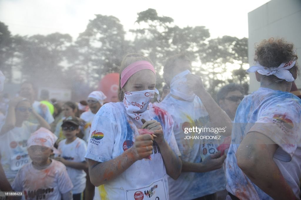 Runners throw paint powder at the starting line of the Kolorfest race in in Guatemala City on February 17, 2013. About 1500 people participated in the event to raise money for charities. AFP PHOTO/Johan ORDONEZ