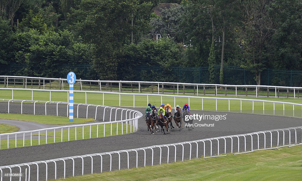 Runners turn into the staright in The Jockey Club Handicap Stakes at Kempton Park racecourse on July 02, 2014 in Sunbury, England.