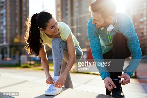 Runners tying running shoes and getting ready to run : Stock Photo