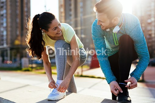 Runners tying running shoes and getting ready to run : Foto de stock