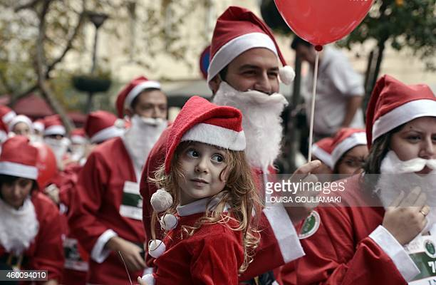 Runners wearing Santa Claus costumes take part in the first Athens 'Santa Claus Run' in city's center on December 7 2014 AFP PHOTO/ LOUISA GOULIAMAKI