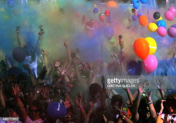 Runners with balloons covered in coloured powder dance after taking part in the Color Run of Sevilla on November 8 2015 The Color Run is a race where...