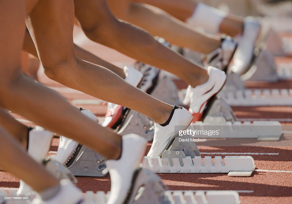 Runners with feet in starting blocks, low section : Stock Photo