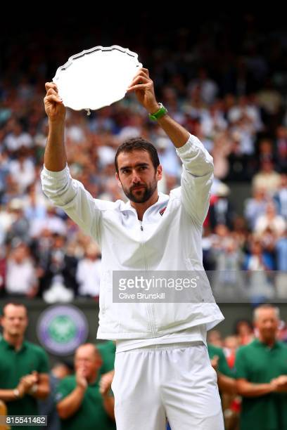 Runnerup Marin Cilic of Croatia poses with his trophy after the Gentlemen's Singles final against Roger Federer of Switzerland on day thirteen of the...