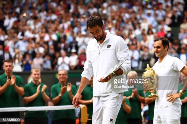 Runnerup Marin Cilic of Croatia walks with his trophy as Roger Federer of Switzerland looks on during the Gentlemen's Singles final on day thirteen...