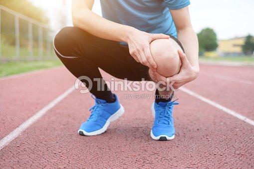 Running athlete feeling pain because of injured knee : Stock Photo