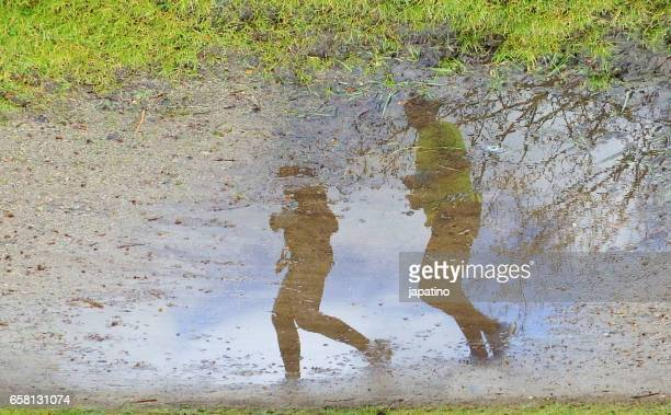 Running athletes reflected in a puddle of water